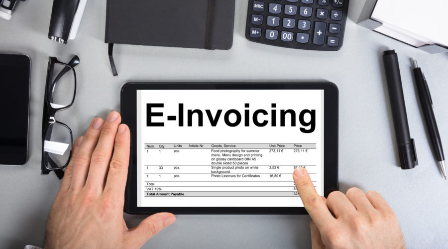 84537680 - directly above shot of businessman's hands going through e-invoicing on digital tablet in office